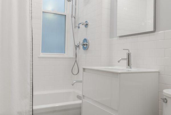 A plain white bathroom with vinyl floor