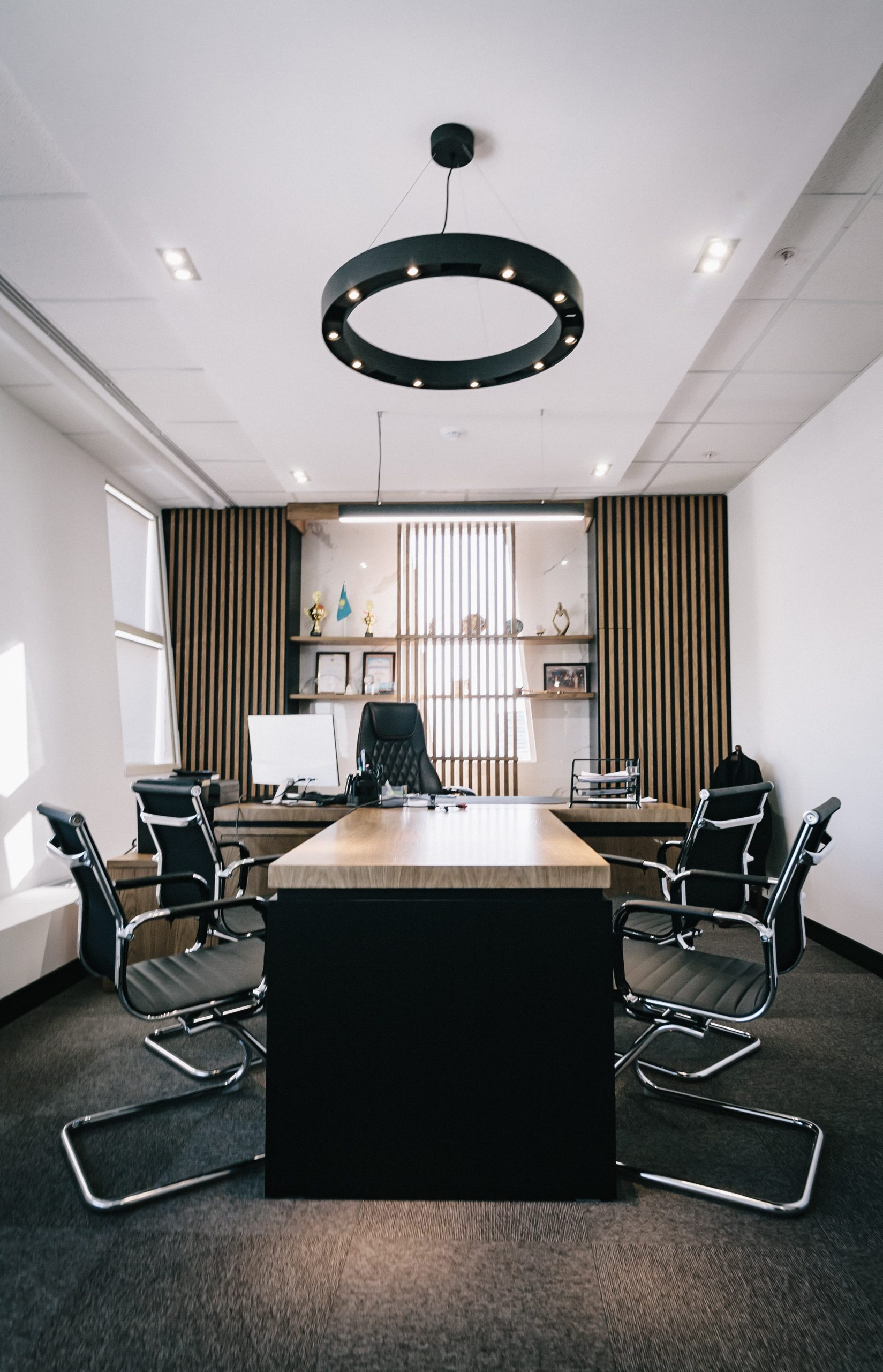 A browns carpet set amongst a stlysih office setting with four chairs.