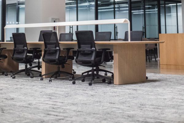 An empty office showing three black chairs and a grey carpet