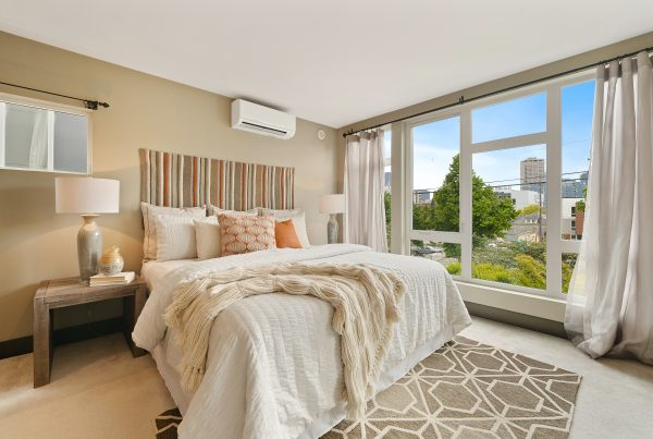 A luxurious bedroom, with a cream throw and patterned rugs
